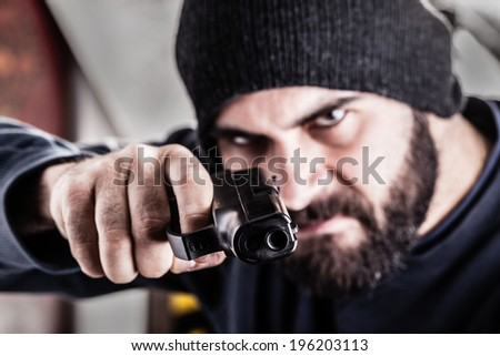 a bearded criminal pointing a pistol and wearing a beanie hat isolated over white - stock photo