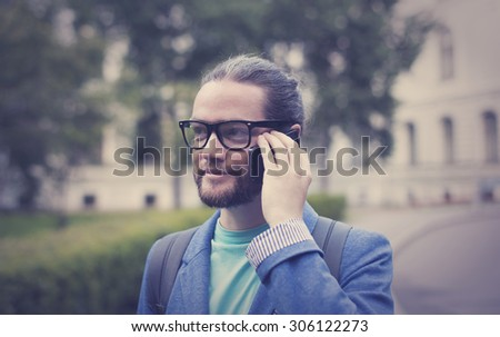 A bearded man in a jacket and sunglasses talking on the phone - stock photo