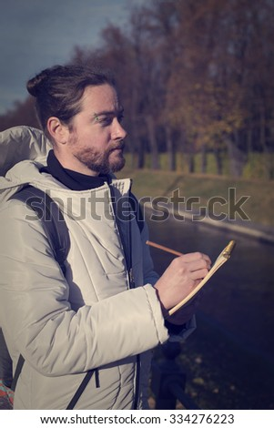 A bearded man in a white jacket with a hood making some notes in pencil in a notebook. - stock photo