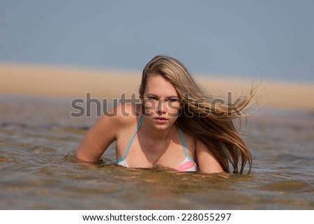 A beautiful and attractive young blonde lady on the beach in South Africa enjoying the summer sun. - stock photo