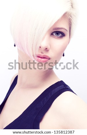 A beautiful and blond scandinavian young woman / model with creative hair style. Toned and natural retouched. - stock photo