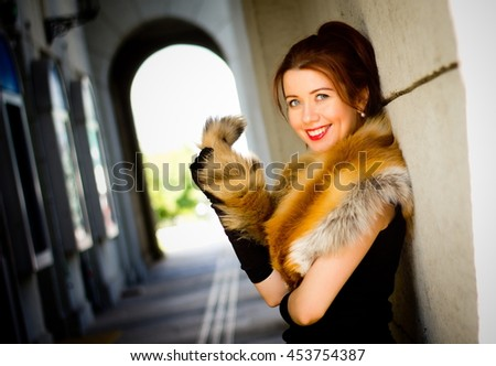 http://thumb101.shutterstock.com/display_pic_with_logo/4367152/453754387/stock-photo-a-beautiful-and-elegant-woman-in-the-fur-coat-fox-fur-is-a-beautiful-arch-with-lanterns-453754387.jpg