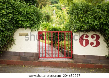A beautiful and homely red gate welcomes to the house - stock photo