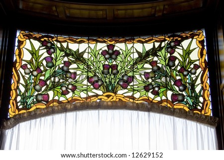 A beautiful antique stained glass window with sun shining through it - stock photo