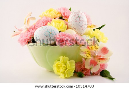 A beautiful arrangement for Easter consisting of decorated eggs and flowers. - stock photo