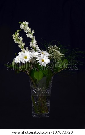 A Beautiful Arrangement of White Flowers in a Crystal Vase on Black - stock photo