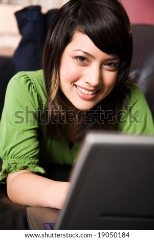 A beautiful asian girl relaxing on the sofa working on the laptop - stock photo