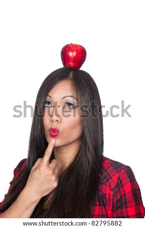 A beautiful Asian woman balances an apple on her head - stock photo