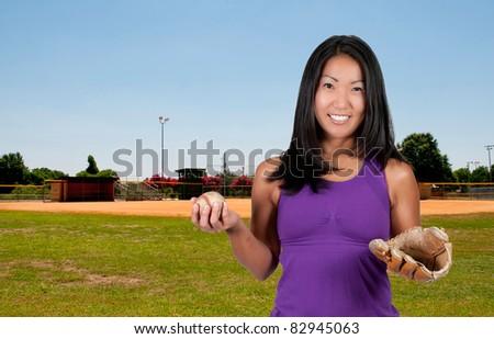 A beautiful Asian woman catching a baseball at a ball field - stock photo