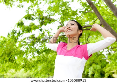 a beautiful asian woman relaxing in the park - stock photo