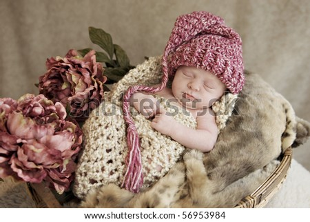 A beautiful baby girl wearing a hat in a blanket cocoon with vintage decorations, soft focus - stock photo