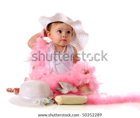 A beautiful baby girl wearing and surrounded with girly-girl goodies -- fancy hats, pearls,and pretty pink boas. - stock photo