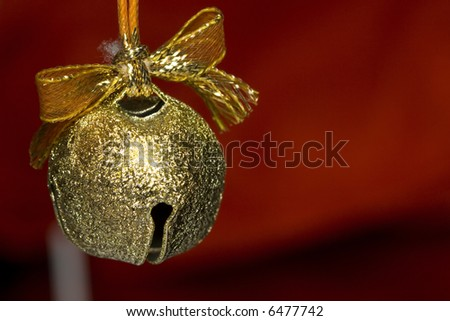 a beautiful background of a gold jingle bell on red background - stock photo