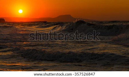 A beautiful beach on a Greek island in summer, under warm sunset light - stock photo