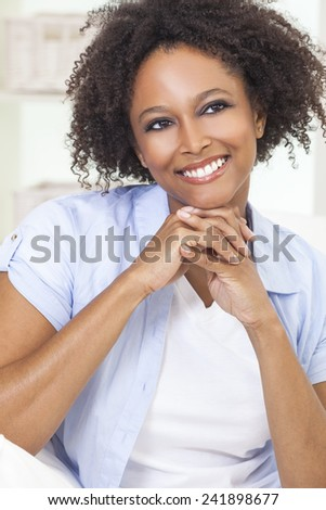 A beautiful black mixed race African American girl or young woman looking happy and smiling - stock photo