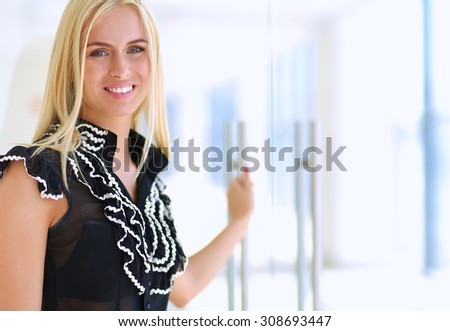 A beautiful blond business woman open the office door - stock photo