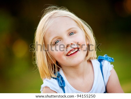 A beautiful blond haired, blue eyed girl joyfully smiles at the camera .  She is in the outdoors - stock photo
