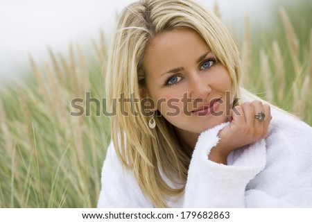 A beautiful blond haired blue eyed model wearing a white toweling robe sits amid tall grass  - stock photo