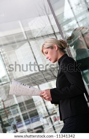 A beautiful blonde business woman reading newspaper - stock photo