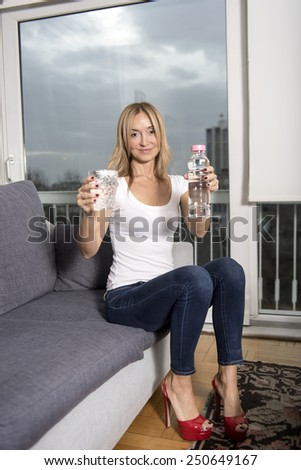 a beautiful blonde girl drinking water.  - stock photo