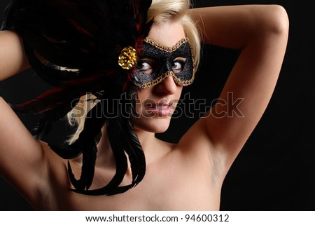 A beautiful blonde girl posing in a studio wearing a black mask on her face. - stock photo