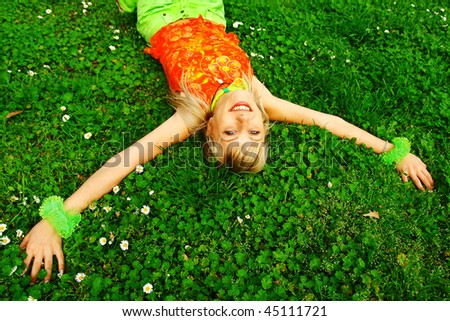 A beautiful blonde laying in a green meadow full of daisies - stock photo