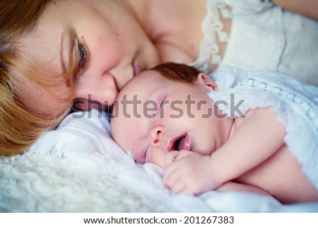 A beautiful blonde loving mother kissing her sleeping 10 days old baby close up - stock photo