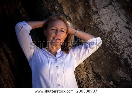 A beautiful blonde mature woman in her late fourties or early fifties is posing for the camera next to the river in Port Alfred South africa. - stock photo