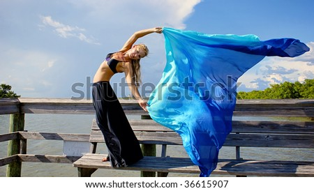 a beautiful blonde woman making eye contact with viewer, her arms raised and her torso twisted towards the viewer, her long veil blowing in the breeze as she poses. with room for copy or text on cloth - stock photo