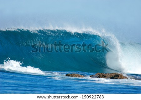 A beautiful blue wave crashes into the rocks at Inhaca Island, Mozambique. - stock photo