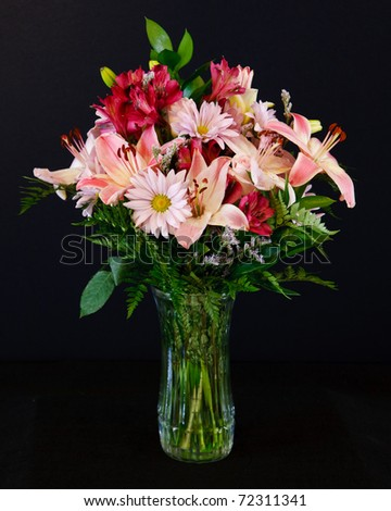 A beautiful bouquet of pink and red lilies, daisies and freesias, with greenery, in a clear glass vase, on a black background - stock photo