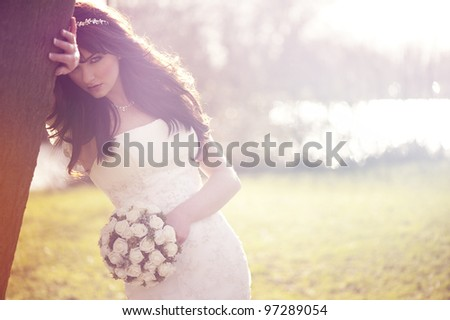 A beautiful bride looking at the camera outdoors. - stock photo