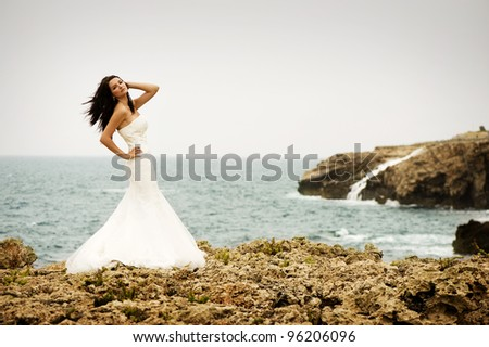 A beautiful bride standing on a cliff on the sea - stock photo