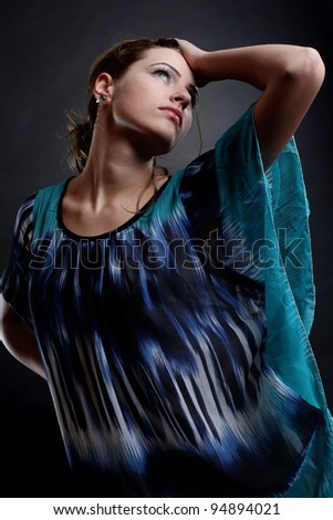 A beautiful brunette girl posing in a studio wearing a coloured skirt.Art photo. - stock photo