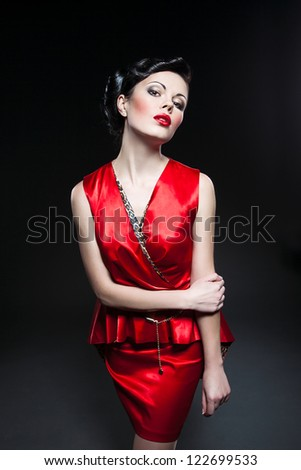 A beautiful brunette in a red dress on a black background - stock photo