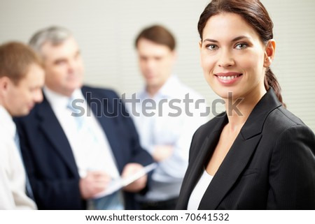 A beautiful businesswoman against her colleagues - stock photo