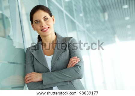 A beautiful businesswoman by wall looking at camera - stock photo