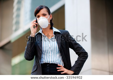 A beautiful businesswoman wearing a mask to represent the tough economic and world times - stock photo