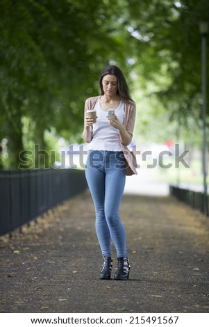 A beautiful caucasian college student using her smartphone. - stock photo