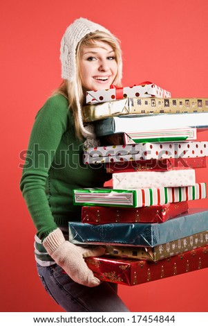 A beautiful caucasian girl carrying many gifts during holiday - stock photo