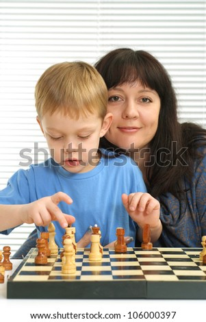 A beautiful Caucasian mother and son playing chess against a light background - stock photo