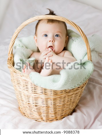 A beautiful caucasian white baby girl portrait with cute facial expression lying in a basket - stock photo