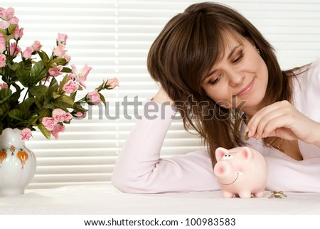 A beautiful charming girl with a piggy bank sitting at a table in a cafe - stock photo