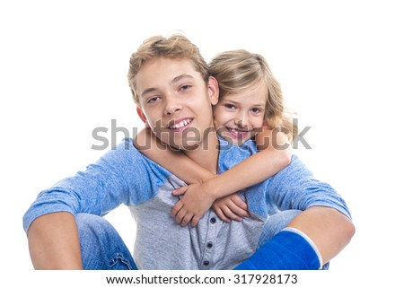 A beautiful children teenager boy with is young sister - stock photo