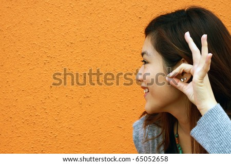 A beautiful Chinese girl hearing the voice - stock photo