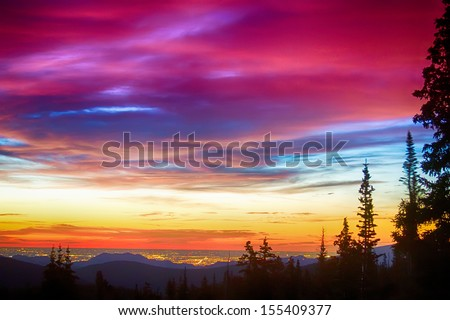 A beautiful colorful epic sunrise over the city lights of Boulder Colorado looking out from high up on the Rocky Mountains Rollins Pass and the Continental Divide west of Boulder.   - stock photo