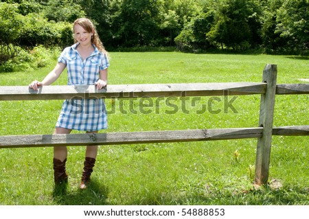 A beautiful country girl standing in a rural setting - stock photo