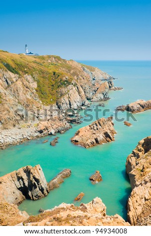 A beautiful cove and rocky cliffs support the Dongju lighthouse along the coastline of Juguang island on the Matsu Islands in Taiwan.  Vertical - stock photo
