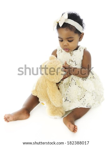 A beautiful, dressed-up baby girl looking her teddy bear over.  On a white background. - stock photo