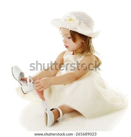 A beautiful, dressed up preschooler putting on her own white shoes.  On a white background. - stock photo